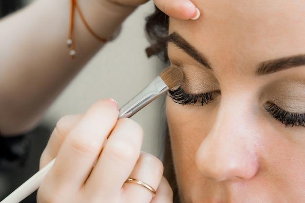 Brosse Avec Fard à Paupières Dans Les Mains D'une Maquilleuse Aux Yeux D'une Fille Dans Un Salon De Beauté Photo Premium