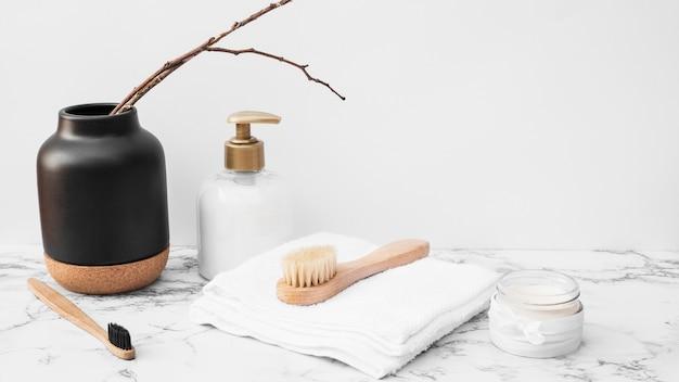 Brosse; serviette; crème hydratante et bouteille cosmétique sur une surface en marbre Photo gratuit