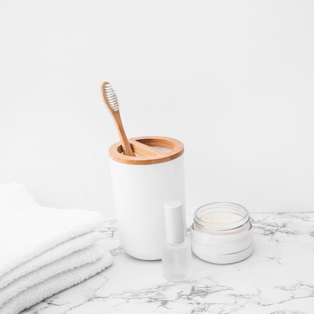 Brosse; les serviettes; vernis à ongles et crème hydratante sur une surface en marbre Photo gratuit