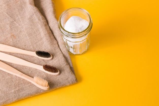 Brosses à Dents En Bambou Et Soda En Pot Sur Fond Jaune Photo Premium