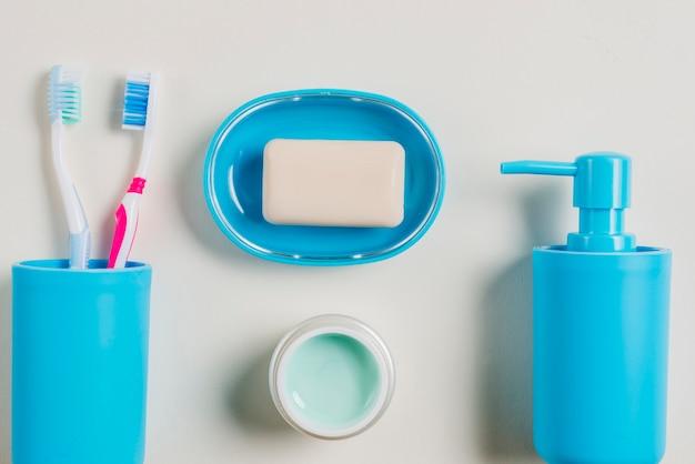 Brosses à dents; crème; distributeur de savon et savon dans un récipient bleu avec de la crème sur fond blanc Photo gratuit