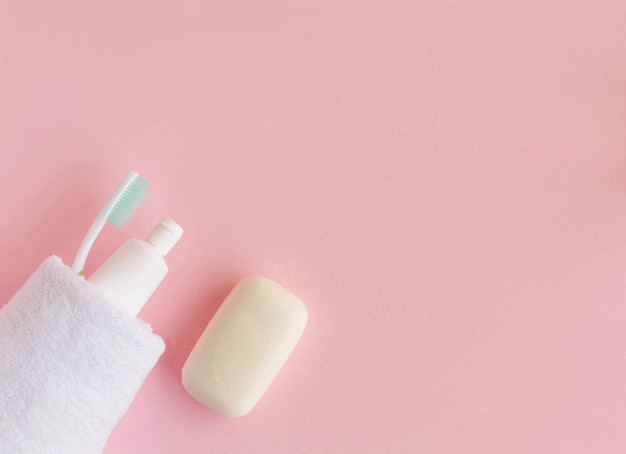 Brosses à dents et dentifrice enveloppés dans une serviette blanche près du savon rose Photo Premium
