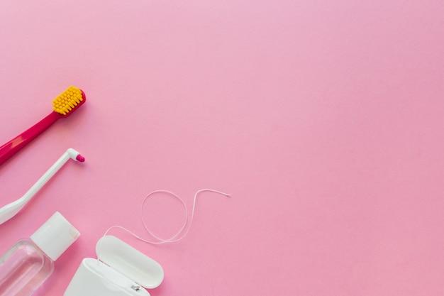 Brosses à dents, fil dentaire et bain de bouche rose Photo Premium