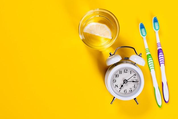 Brosses à Dents, Verre D'eau Au Citron Et Réveil Photo Premium