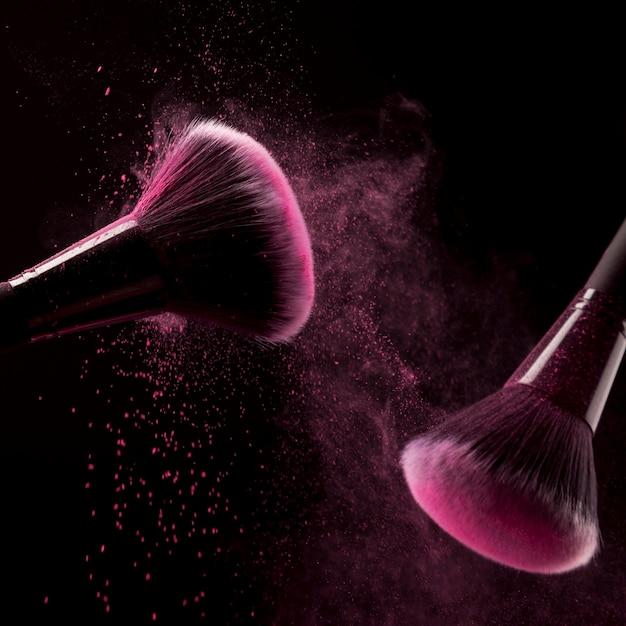 Brosses avec des particules de poudre rose Photo gratuit