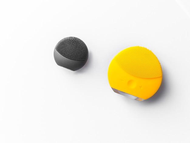 Brosses en silicone noir et jaune pour le visage laver et spa visage isolé sur fond blanc. Photo Premium