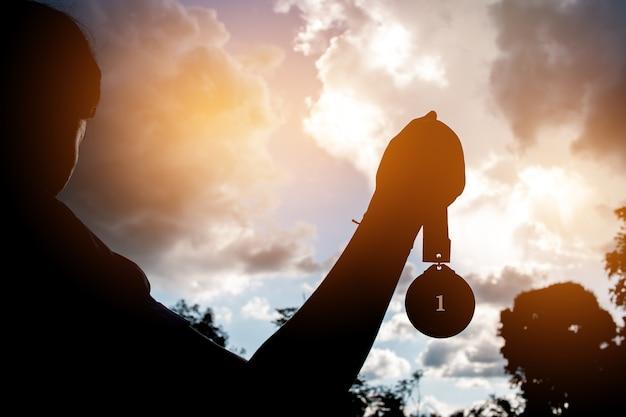 Brouillé De Silhouette Busunesswoman Mains Levées Et Tenant Des Médailles D'or Avec Un Ruban Contre Le Fond Du Coucher Du Soleil Pour Montrer Le Succès De L'équipe Dans Les Entreprises, Winners Succès Concept De Récompense. Photo Premium