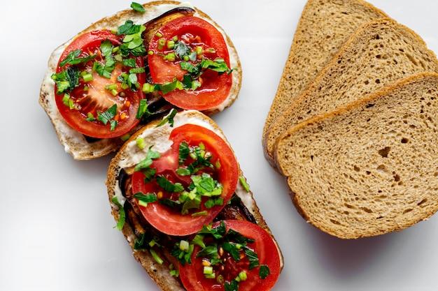 Brown Fait Griller Des Tranches De Pain Chaud Avec Des Tomates En Tranches Rouges Et Des Aubergines Noires Frites Avec Des Verts Sur Le Sol Blanc Photo gratuit