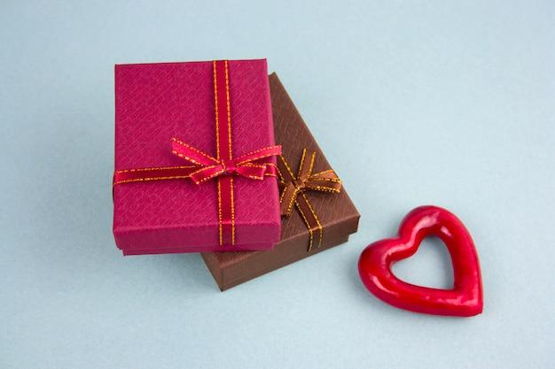 Brownand rouge boîtes présent et fond bleu coeur vue de dessus coeur rouge Photo Premium
