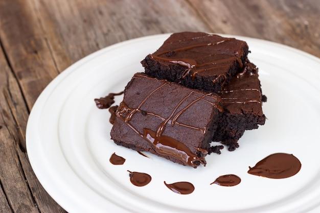 Brownie fait maison avec du fudge au chocolat. dessert sucré sur fond en bois. Photo Premium