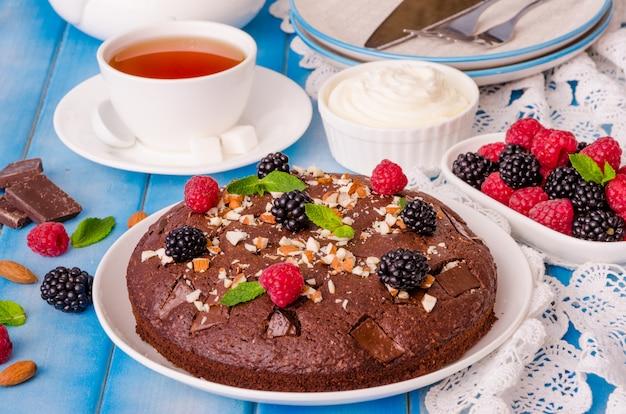 Brownie gâteau au chocolat avec framboises, mûres, amandes et crème fouettée sur fond en bois. Photo Premium
