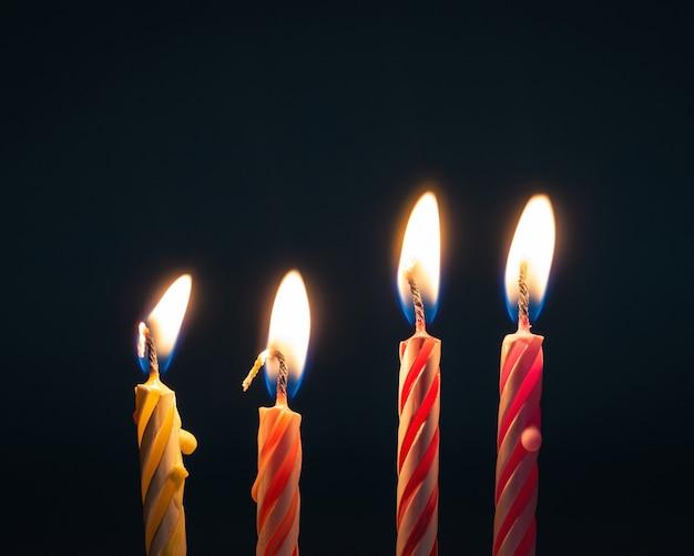 Brûler des bougies d'anniversaire sur un fond sombre avec le feu. Photo Premium