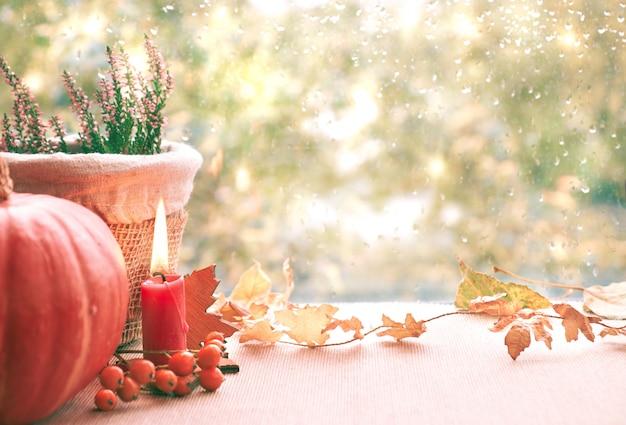 Brûler des bougies, des citrouilles, des bruyères et des décorations d'automne sur un tableau de fenêtre un jour de pluie Photo Premium