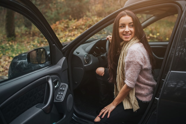 Brune Aux Cheveux Longs Sur L'auto. Un Modèle Féminin Porte Un Pull Et Une écharpe. L'automne . Voyage En Forêt D'automne En Voiture Photo Premium