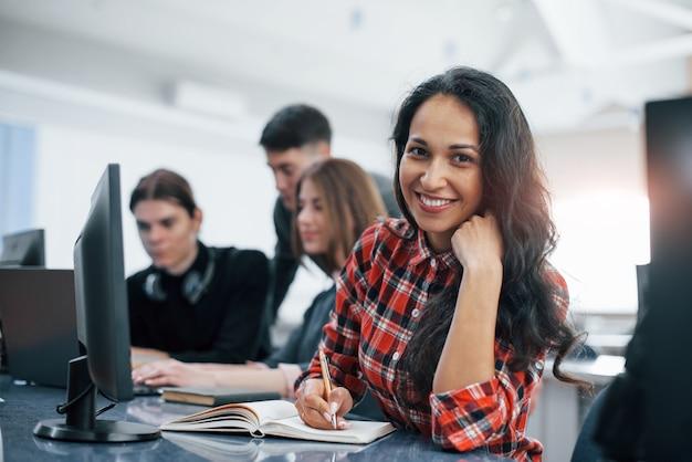 Brune Joyeuse. Groupe De Jeunes En Vêtements Décontractés Travaillant Dans Le Bureau Moderne Photo gratuit