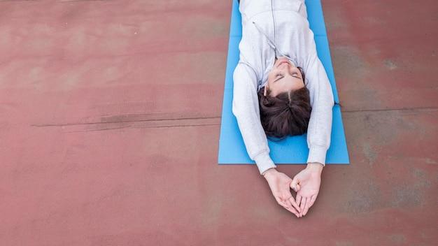 Brunette blogueuse enregistrant une routine de yoga Photo gratuit