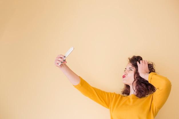 Brunette blogueuse faisant un selfie Photo gratuit
