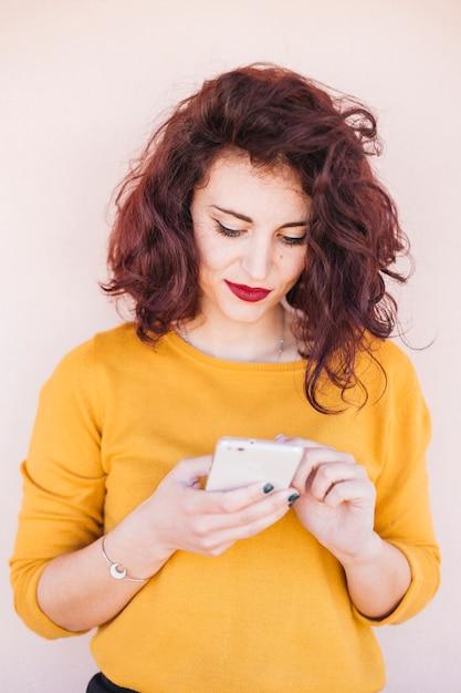 Brunette blogueuse utilisant son téléphone portable Photo gratuit