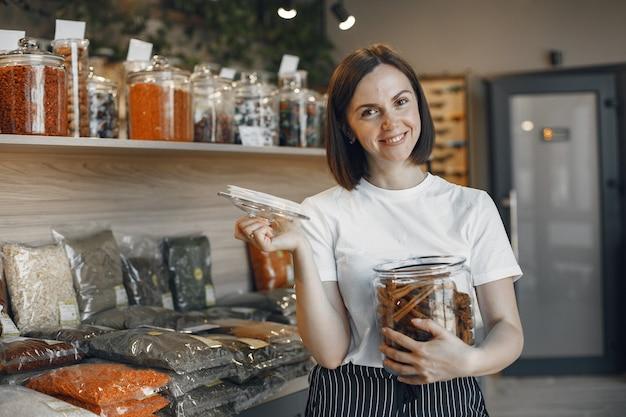 Brunette Choisit La Nourriture. Dame Tenant Un Pot De Cannelle. Fille Dans Une Chemise Blanche Au Supermarché. Photo gratuit