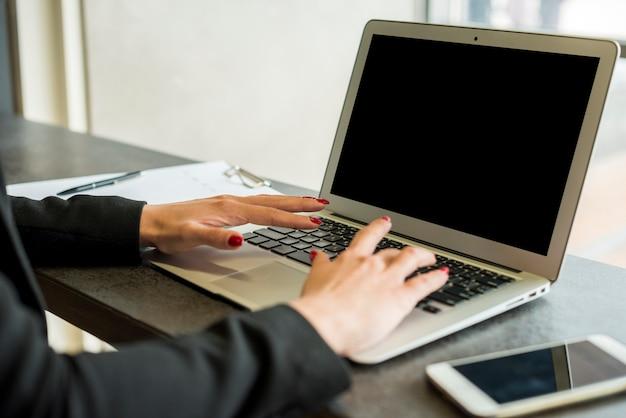 Brunette femme d'affaires à l'aide d'un ordinateur portable Photo gratuit