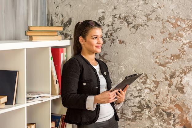 Brunette femme d'affaires à l'aide de sa tablette Photo gratuit