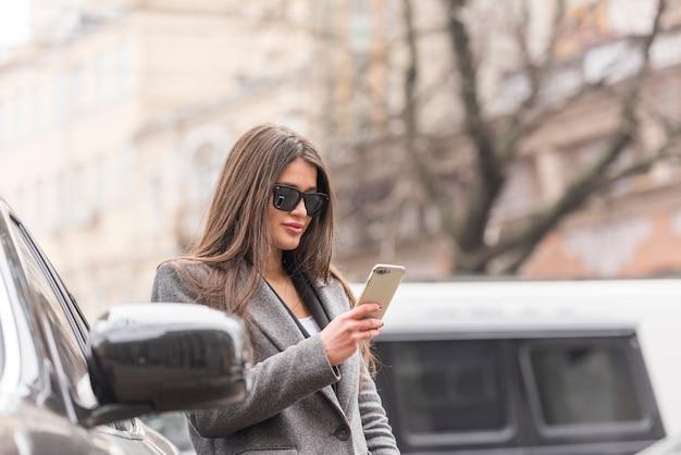 Brunette femme d'affaires à l'aide de son smartphone Photo gratuit