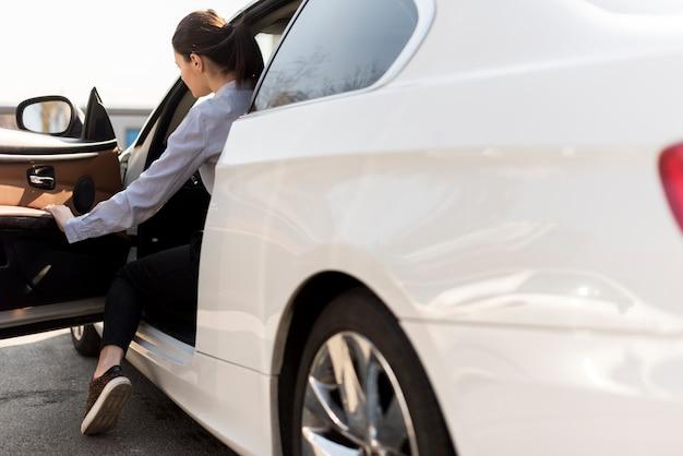 Brunette femme d'affaires avec détail de voiture Photo gratuit