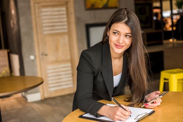 Brunette femme d'affaires écrit sur un document Photo gratuit