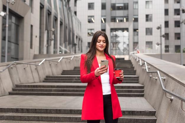 Brunette femme d'affaires à l'extérieur avec manteau de lecture Photo gratuit