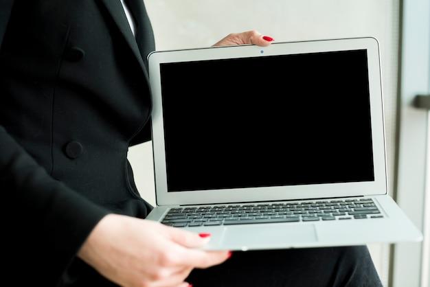 Brunette femme d'affaires montrant un ordinateur portable Photo gratuit