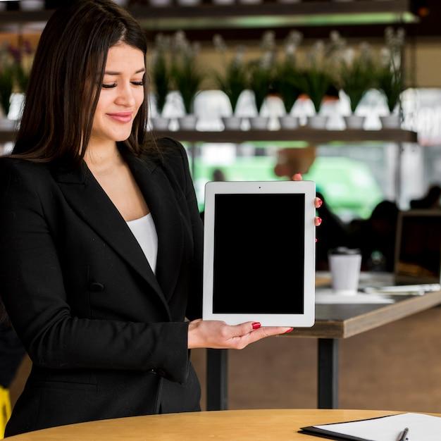 Brunette femme d'affaires montrant une tablette Photo gratuit