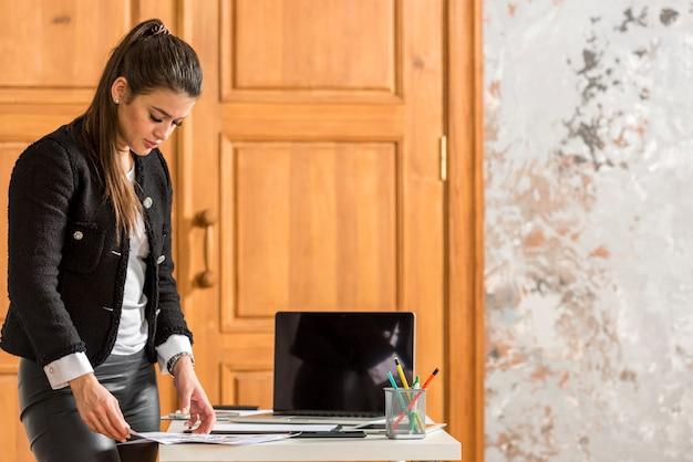 Brunette femme d'affaires organisant ses papiers Photo gratuit