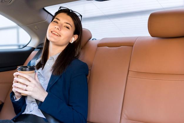 Brunette femme d'affaires posant à l'intérieur d'une voiture Photo gratuit