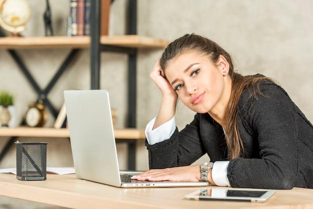 Brunette femme d'affaires s'ennuie à son bureau Photo gratuit