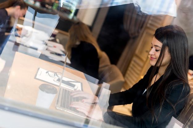 Brunette femme d'affaires à travers une fenêtre avec l'ordinateur portable Photo gratuit