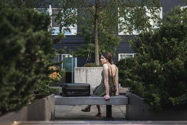 Brunette femme assise sur un siège en ciment sur parc urbain Photo gratuit