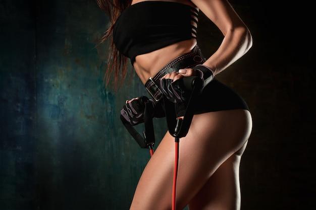 Brunette Femme Athlétique Exerçant Avec Du Ruban De Caoutchouc Photo gratuit