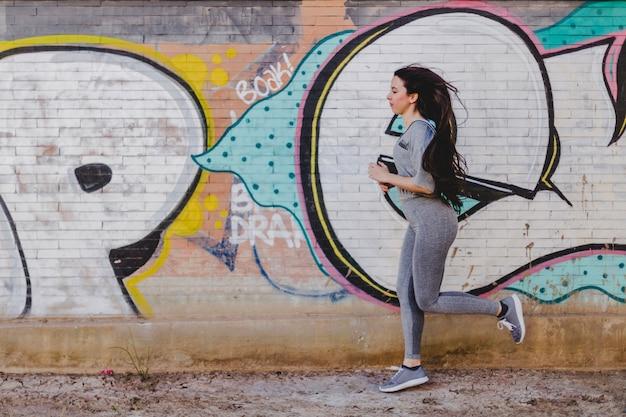 Brunette Femme Coulant Contre Le Mur De Béton Photo gratuit
