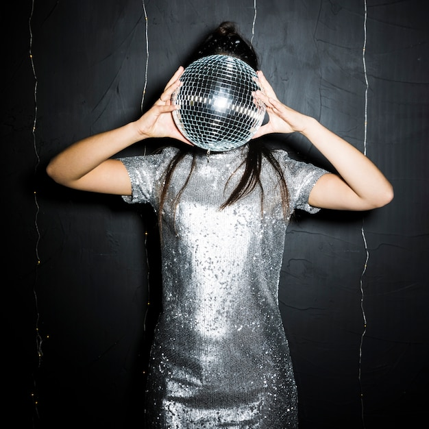 Brunette femme fermant le visage par une boule disco Photo gratuit