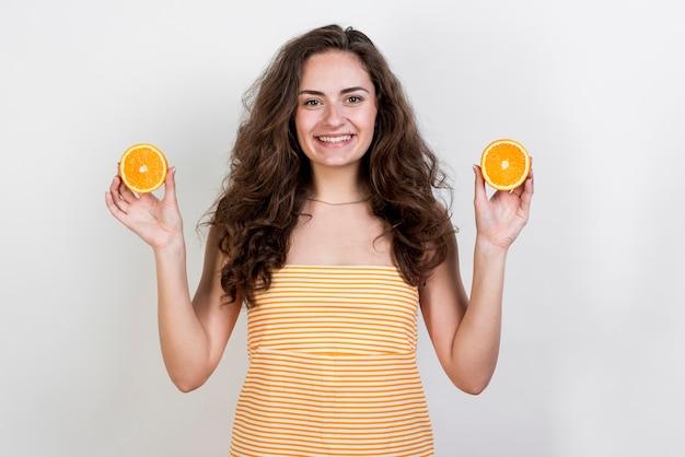 Brunette femme tenant une orange Photo gratuit