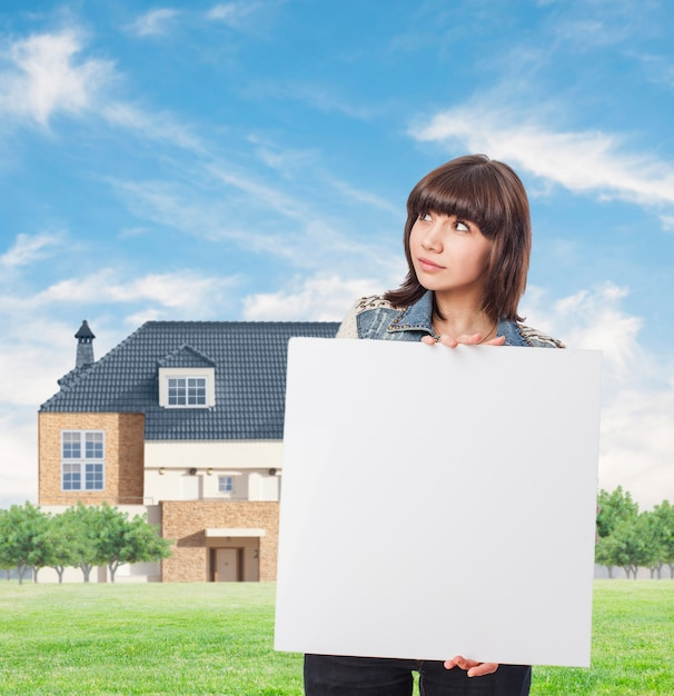Brunette femme tenant un tableau blanc avec la maison de fond Photo gratuit