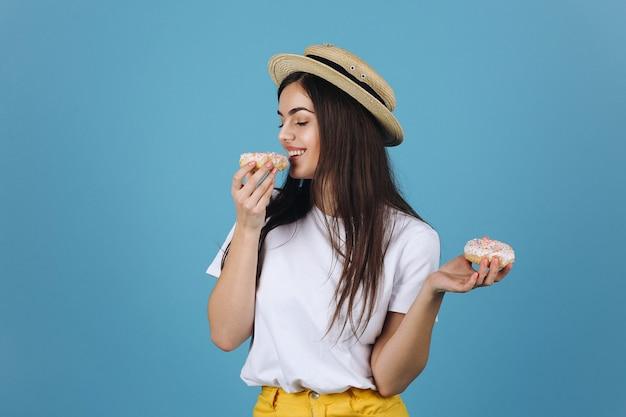 Brunette fille goûte un beignet posant dans un chapeau Photo gratuit