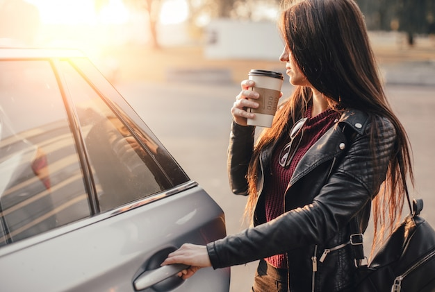 Brunette Jeune Femme Avec Smartphone Et Tasse De Café Noir Près De Voiture Neuve Au Parking De La Ville Photo Premium