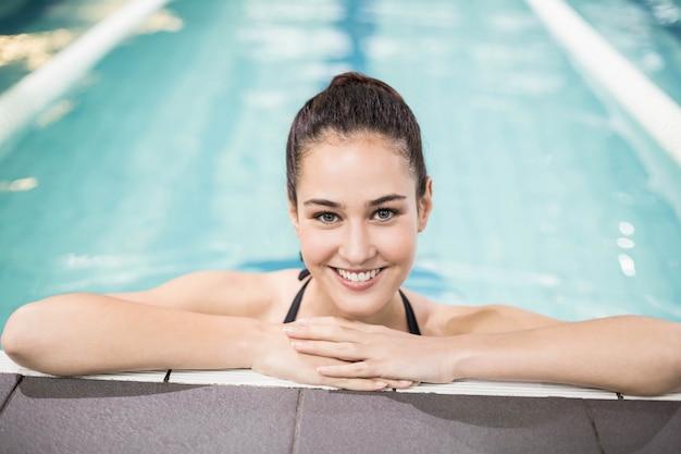 Brunette souriante se penchant sur le bord de la piscine en piscine Photo Premium