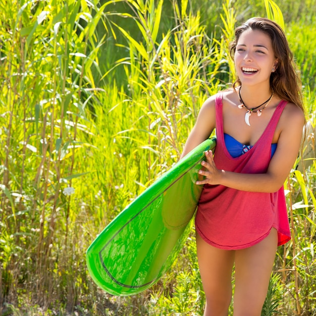 Brunette surfeuse marchant dans la jungle Photo Premium