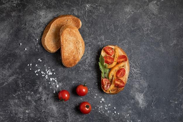 Bruschetta aux tomates dans les mains sur un fond sombre, vue de dessus. Photo Premium