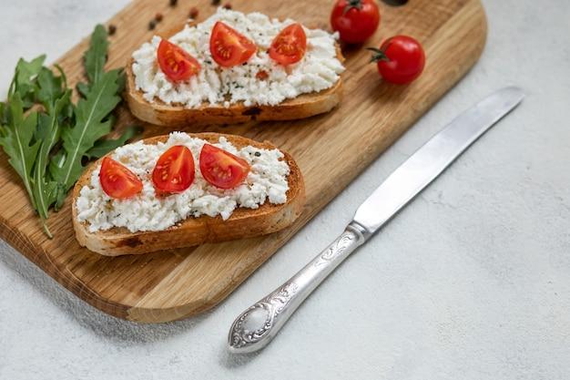 Bruschetta italienne avec tomates rôties, fromage mozzarella et fines herbes sur une planche à découper. Photo Premium