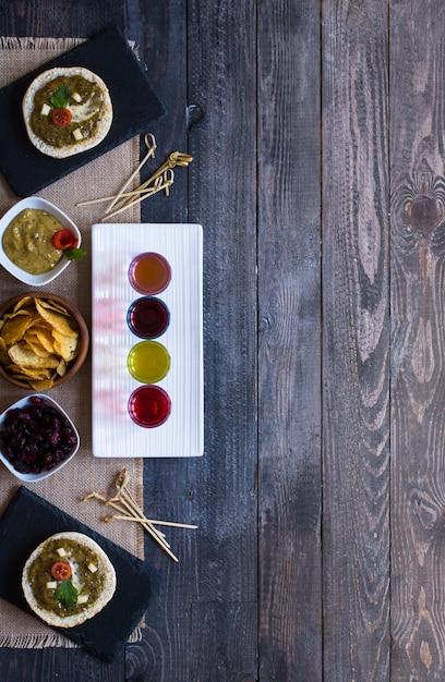 Bruschetta savoureuse et délicieuse avec tomates à l'avocat, fromage, chips d'herbes et liqueur sur un fond en bois. Photo Premium