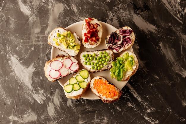Brushetta ou tapas espagnoles traditionnelles. des amuse-gueules aux antipasti italiens sur une planche de bois. Photo Premium