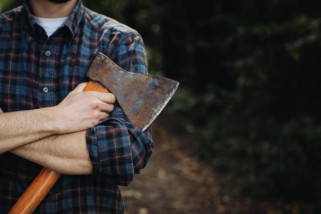 Bûcheron barbu fort tenant une hache dans les bois Photo Premium
